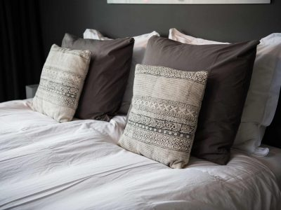 Gray color scheme pillows setting on bed with satin finished style bedding