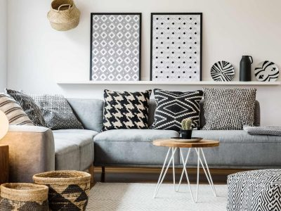 Patterned pillows on grey corner sofa in apartment interior with